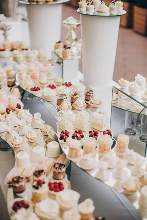 stylish pink candy bar table with delicious cakes,cookies,cupcakes with fruits in pink and white colors. luxury catering in restaurant. modern wedding reception. sweet table Stock Photo