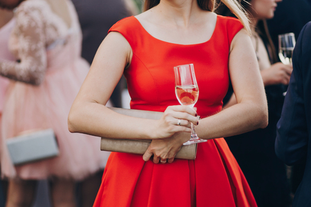 hands of stylish people cheering with glasses of champagne, luxury wedding reception, rich celebration.  guests toasting at christmas luxury celebration feast Stock Photo