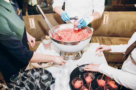 big bowl of strawberry organic ice cream.master class of making natural fruit ice cream. confectioner making homemade ice cream at wedding reception in restaurant.