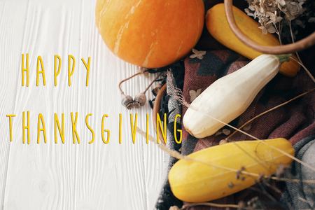 Happy Thanksgiving text, seasons greeting card. Thanksgiving sign. Pumpkin ,zucchini , wicker basket on white wooden background.  Fall Harvest