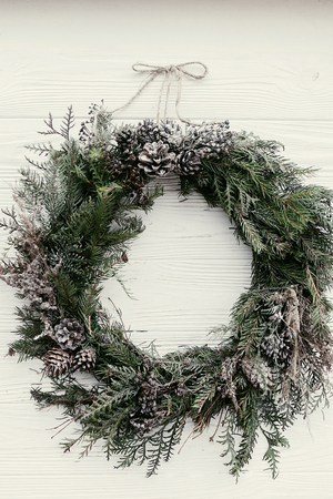 Christmas wreath. stylish rustic christmas wreath on white wooden door with pine cones,fir branches,snow. space for text. handmade decor for winter holidays. Stock Photo