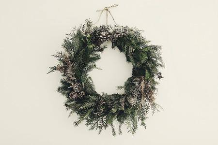 moderner Weihnachtskranz. stilvoller rustikaler Weihnachtskranz mit Tannenzapfen, Tannenzweigen, Schnee, hängend an weißer Wand. Platz für Text. handgemachtes Dekor für Winterferien