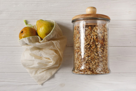 granola in glass and eco natural bags with fruits, flat lay. plastic free items. reuse, reduce, recycle, refuse. bulk store. sustainable lifestyle concept. zero waste. Stock Photo