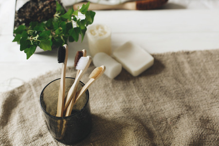eco natural bamboo toothbrushes in glass on rustic background with greenery. sustainable lifestyle concept. zero waste home. bathroom essentials, plastic free items Standard-Bild