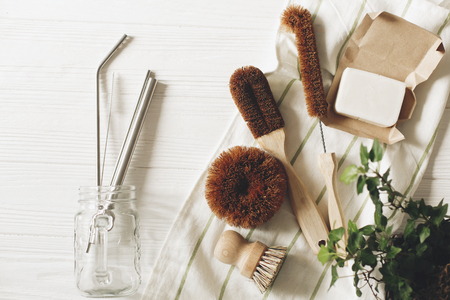 eco natural coconut soap and brushes for washing dishes, metal straws, eco friendly flat lay. sustainable lifestyle concept. zero waste food cleaning. plastic free items. reuse, reduce