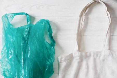 Plastik verbieten. Plastiktüte mit Öko natürlichen wiederverwendbaren Einkaufstasche zum Einkaufen, flach auf rustikalem Hintergrund liegen. nachhaltiges Lifestyle-Konzept. kein Verlust. kunststofffreie Gegenstände. wiederverwenden, reduzieren, ablehnen, Standard-Bild