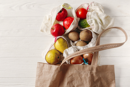 zero waste food shopping. eco natural bags with fruits and vegetables in tote, eco friendly, flat lay. sustainable lifestyle concept. plastic free items. reuse, reduce, recycle, refuse.