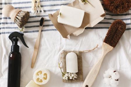 concepto de desperdicio cero, plano de artículos sin plástico. luffa natural, cepillo de dientes de bambú, cepillo, jabón de coco, detergente hecho a mano y desodorante de cristal en una toalla, artículos de baño ecológicos