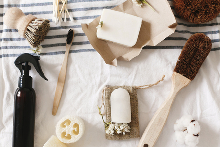zero waste concept, flat lay of plastic free items. natural luffa, bamboo toothbrush, brush, coconut soap, handmade detergent and crystal deodorant on towel, eco bathroom essentials