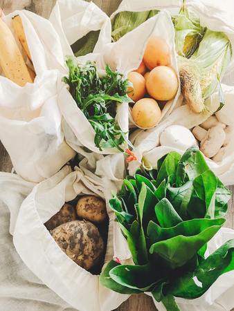 fresh vegetables in eco cotton bags on table in the kitchen. lettuce, corn, potatoes, apricots, bananas, rucola, mushrooms from market. zero waste shopping concept.   ban plastic Stock Photo