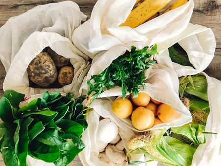 zero waste shopping concept. fresh vegetables in eco cotton bags on table in the kitchen. lettuce, corn, potatoes, apricots, bananas, rucola, mushrooms from market. ban plastic