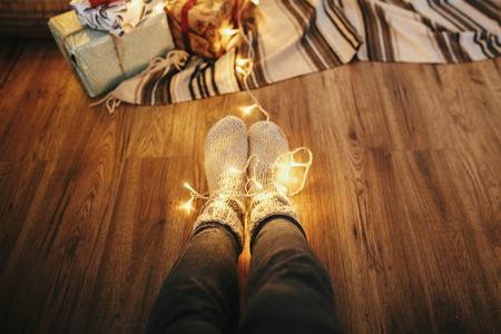 girl legs in stylish warm sock sitting with garland lights at christmas tree with gifts. socks on floor  rug in festive room. decor for winter holidays. atmospheric moment Stock Photo