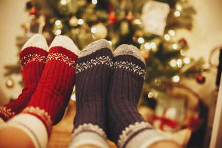 stilvolle festliche Socken auf Paarbeinen auf Hintergrund des goldenen schönen Weihnachtsbaumes mit Lichtern im festlichen Raum. Zeit zum Entspannen mit der Familie. gemütliche Winterferien. warmer atmosphärischer Moment