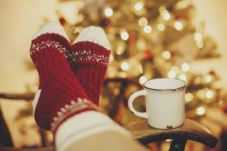 festive socks and mug with hot drink on old wooden chair on background of golden beautiful christmas tree with lights in festive room. cozy winter holidays. warm atmospheric moment Фото со стока