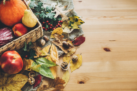 Hello Autumn. Pumpkin and vegetables in basket and colorful leaves with acorns and nuts on wooden table, top view. Bright Fall image. Harvest time. Happy Thanksgiving flat lay