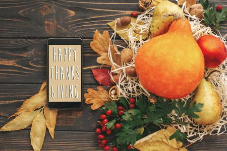 Happy Thanksgiving Text on Phone empty screen and beautiful Pumpkin with bright autumn leaves, acorns, nuts, berries on wooden rustic table, flat lay. . Seasons greeting card. Foto de archivo - 108580616