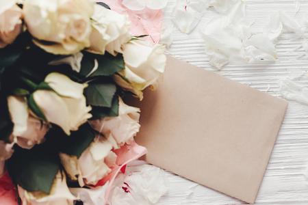 White roses with empty card on wooden background, flat lay with space for text. Floral greeting card mockup. Wedding invitation,happy mother day concept. Valentine day