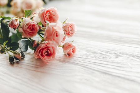 Pink small roses on wooden background in light, space for text. Floral greeting card mockup. Wedding invitation,happy mother day or Valentine day concept. Tender Flowers image Standard-Bild - 108582246