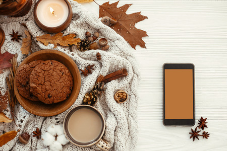 Stylish Autumn Flat Lay. Phone with empty screen and coffee,cookies, leaves, candle, nuts, acorns, cotton, cinnamon on sweater and white rustic background. Space for text