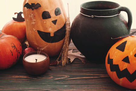 Happy Halloween concept. Pumpkins, jack-o-lantern, witch cauldron,bats, spider, candle, autumn leaves on black wood in light. Space for text. Seasons greeting Stock Photo