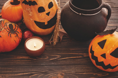 Pumpkins, jack-o-lantern, witch cauldron,bats, spider, candle light, autumn leaves on dark background. Space for text. Halloween decorations. Seasons greeting. Happy Halloween