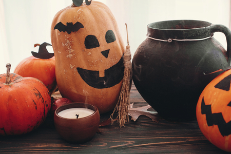 Pumpkins, jack-o-lantern, witch cauldron,bats, spider, candle, ghost, autumn leaves on black wood in light. Space for text. Halloween decorations. Seasons greeting. Happy Halloween Stock Photo