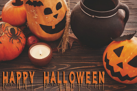 Happy Halloween text, bloody sign on pumpkins, jack-o-lantern, witch cauldron,bats, spider, candle,ghost, autumn leaves on dark background. Space for text. Halloween decorations. Seasons greeting Stock Photo