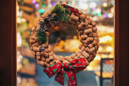 Creative christmas wreath of wine corks, pine cones and red bow on door or window in european city street. Stylish christmas street decor, Festive decorations and illumination. Winter holidays