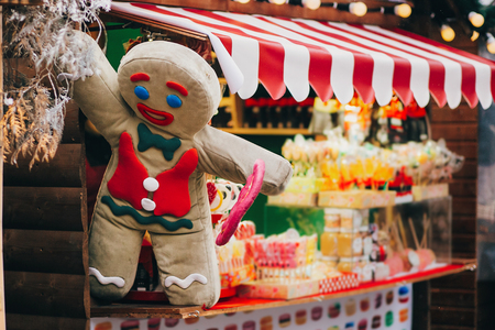 Gingerbread cookie man with lollipop on christmas market cabin. Winter holiday fair in european city street. Candy shop. Festive decor and illumination in city center, winter holidays Stock Photo