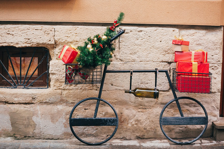 Creative bicycle with christmas tree,red presents, wine bottle in european city street. Stylish christmas street decor, Festive decorations and illumination. Winter holidays. Wine shop Stock Photo
