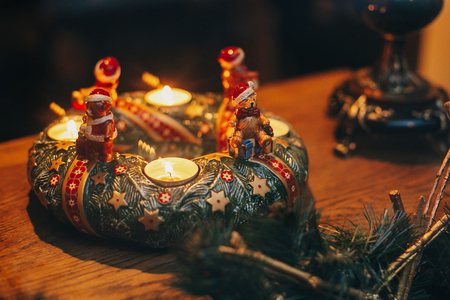 Vintage Christmas wreath with candles and bear toys on wooden table in european city street. Festive decorations and illumination in winter holidays in town.