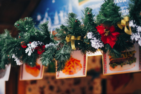 Stylish garland lights and fir branches with christmas decorations,bows,snow  on wooden cabins at european city market. Festive street decor in winter holidays Stock Photo
