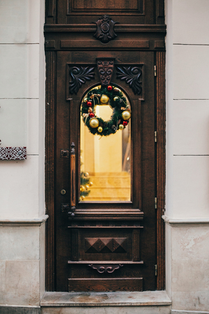Traditional christmas wreath with red ornaments and gold baubles on old wooden door in european city street. Stylish christmas street decor, Festive decorations and illumination. Winter holidays