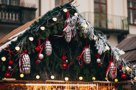 Stylish garland lights and fir branches with christmas decorations, silver pine cones and red ornaments on wooden cabins at european city market. Festive street decor in winter holidays Stock Photo