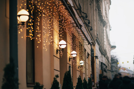 Stylish christmas decorations, garland lights and lamps on old building and crowd of people in european city street. Festive decor and illumination in city center, winter holidays