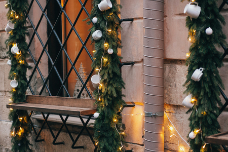 Stylish  christmas decorations, white ceramics cups of coffee or tea, garland lights and fir branches on window of cafe or coffee shop in european city street. Creative festive decor Stock Photo