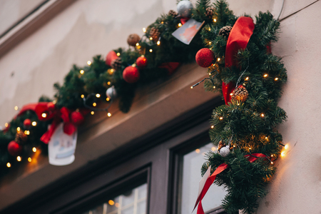 Stylish christmas decorations, garland lights and fir branches with red ornaments on window in european city street. Festive decor and illumination in winter holidays city center Stock Photo