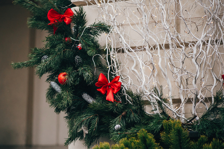 Stylish christmas wreath with red bows and ornaments, pine cones, stars, white branches on building in european city street. Festive decor in city center, winter holidays