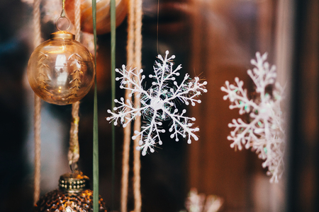 Stylish christmas decorations, snowflake, acorn ornament, toys in window in european city street. Festive decor in city center, winter holidays Stock Photo