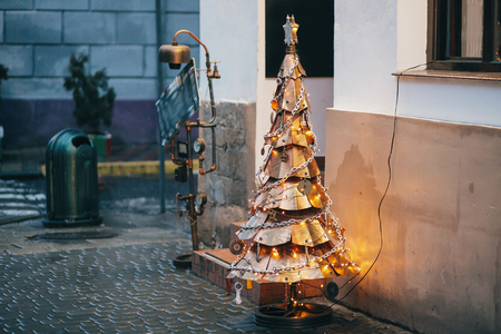 Steampunk christmas tree. Creative Steampunk steel tree with metal ornaments and branches, stylish christmas decorations and garland lights in european city street. Festive decor Stock Photo