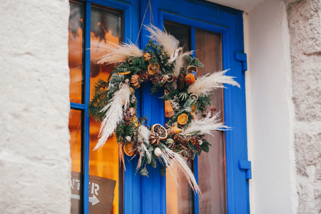 Modern christmas wreath with oranges,herbs, rustic ornaments, pine cones, branches on blue door in european city street. Festive decorations and illumination in city center,