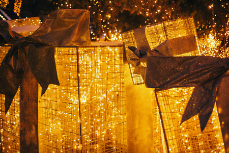 Golden gift boxes with lights under christmas tree in evening european city center. Big presents with bows and illumination on background of lights. Festive decor in winter holidays