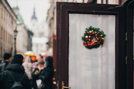 Traditional christmas wreath with red baubles and gold ornaments with lights on old door in european city street. Stylish christmas street decor, Festive decorations and crowd of people