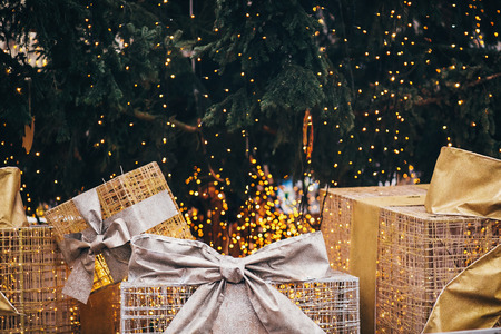 Golden gift boxes under christmas tree in european city center. Big presents with bows on background of christmas lights. Festive decor of city streets in winter holidays