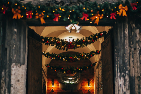 Stylish christmas decorations, jingle bells, garland lights, fir branches with ornaments  in hall  indoors in european city street. Festive decor and illumination in city center, winter holidays Stock Photo