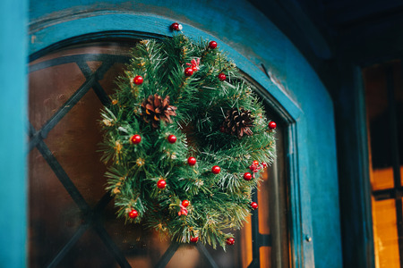 Traditional christmas wreath with red berries and pine cones on old blue door in european city street. Stylish christmas street decor, Festive decorations and illumination. Winter holidays