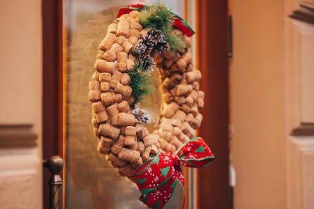 Corona de Navidad creativa de corchos de vino, piñas y lazos rojos en la puerta o ventana de la tienda de vinos en la calle de la ciudad europea. Elegante decoración de calle navideña, decoraciones festivas.
