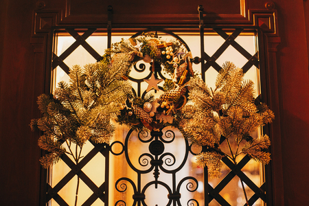 Modern christmas wreaths with  gold ornaments, pine cones, branches on door with lights in night city street. Festive decorations and illumination in city center, winter holidays Stock Photo