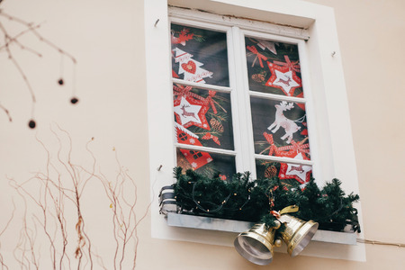 Stylish christmas decorations, jingle bells, garland lights, fir branches,reindeers  on window in european city street. Festive decor and illumination in city center, winter holidays Stock Photo