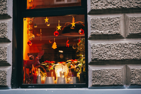 Stylish christmas decorations, reindeer toys, christmas trees, pine cones, lights in window in european city street. Festive decor and illumination in city center, winter holidays Stock Photo